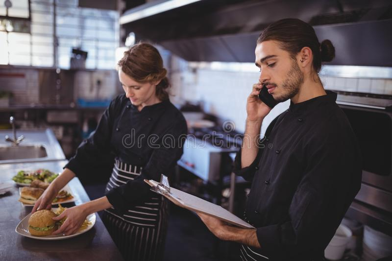 年轻侍者谈话在智能手机,当准备食物的女服务员在商业厨房里时 免版税库存图片