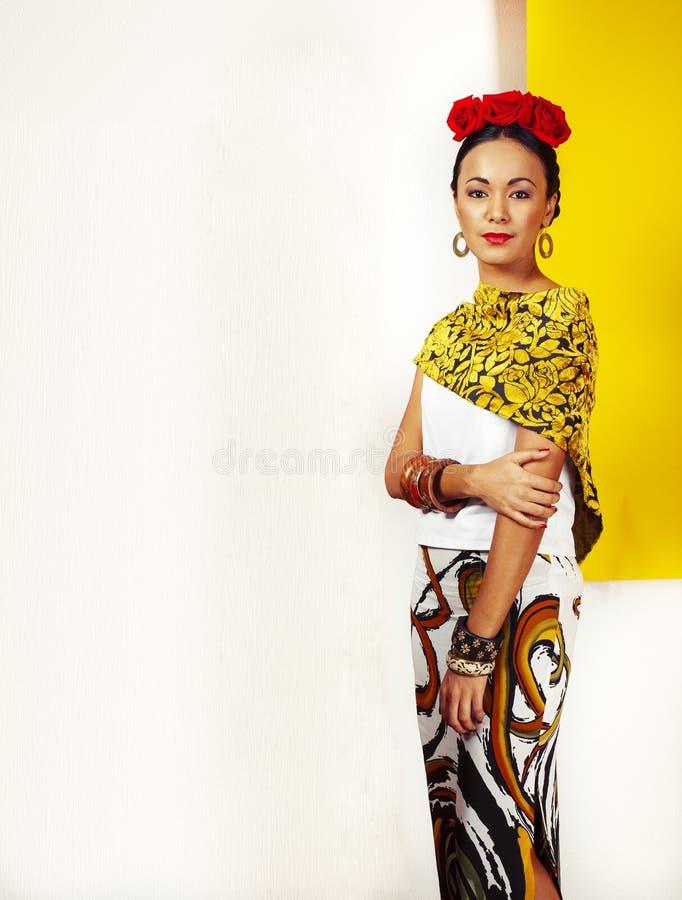 年轻俏丽墨西哥妇女微笑愉快在黄色背景,生活方式人概念 免版税库存照片