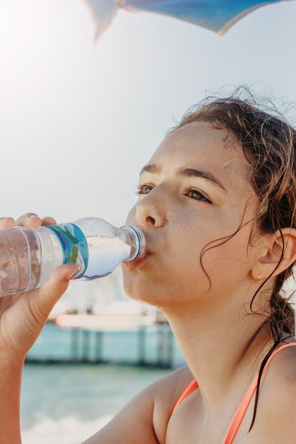年轻俏丽的从瓶的少年女孩饮用水在海附近的海滩 免版税库存图片