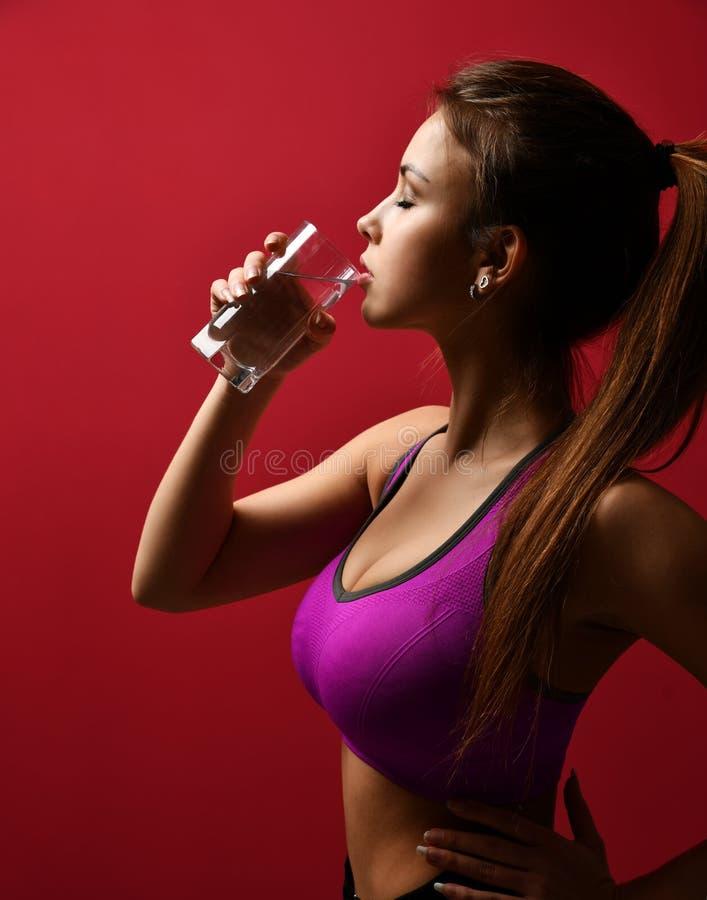 年轻俏丽的在紫色体育胸罩的妇女饮用水 免版税库存照片