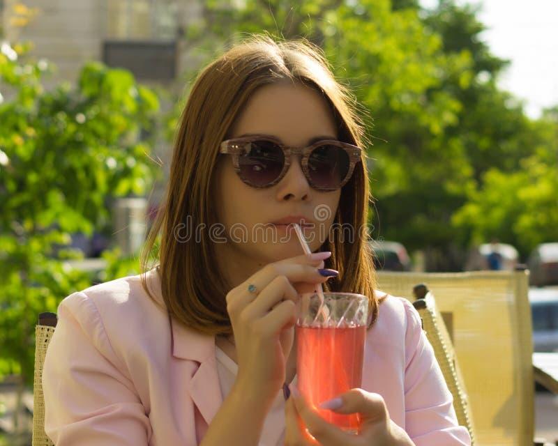 年轻俏丽的女孩喝一个冷的饮料,室外 免版税库存图片