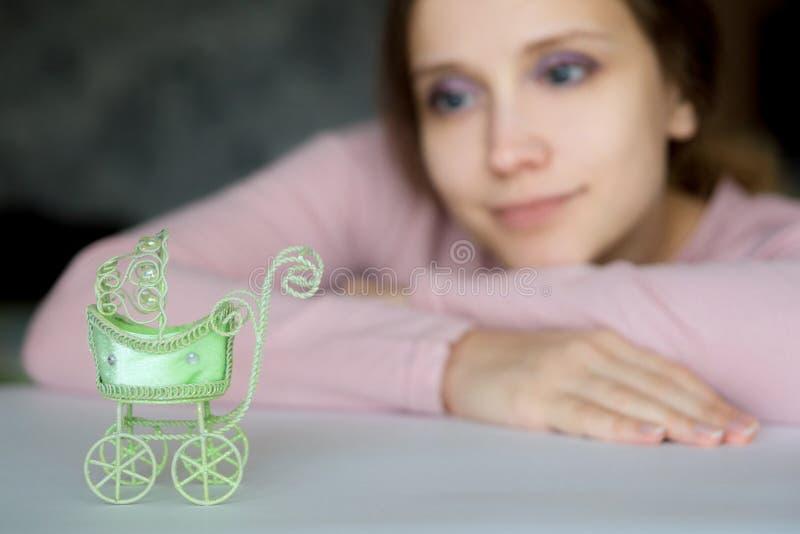 年轻俏丽的女孩看有希望地摇篮车玩具 免版税图库摄影