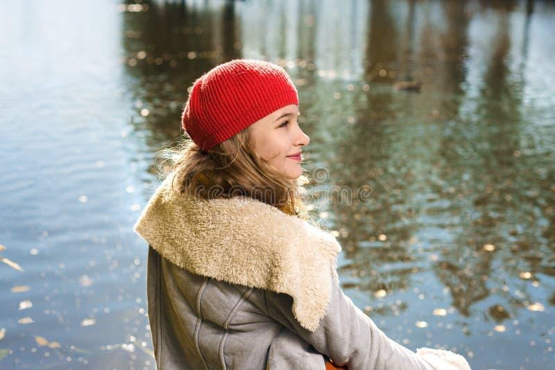 年轻俏丽的女孩秋天画象红色帽子的 库存照片