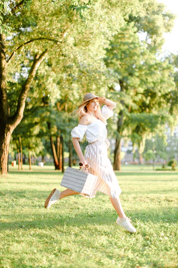 年轻俏丽的女孩跳跃在公园和跑,佩带时装和帽子 免版税库存照片