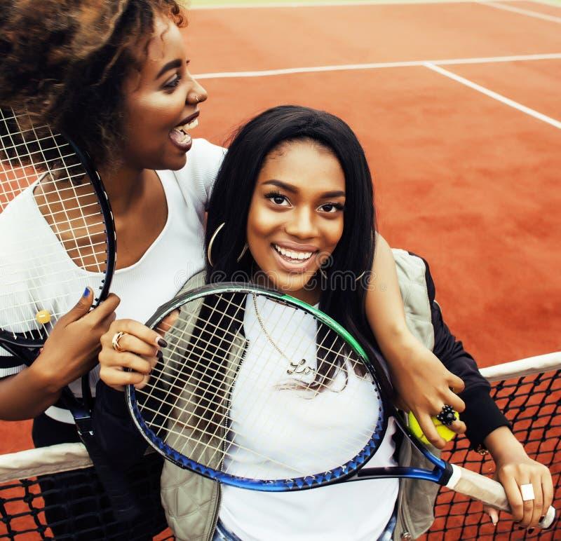 年轻俏丽的女朋友垂悬在网球场的,时尚stylis 免版税库存图片