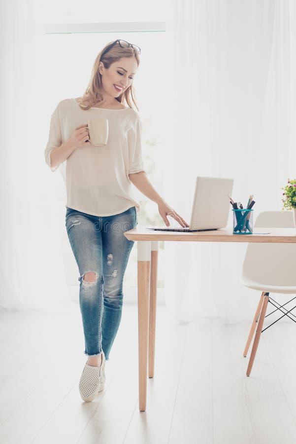年轻俏丽的妇女与站立近的在netwbook的膝上型计算机一起使用桌键入的电子邮件信件 站立在白光室享用 库存照片