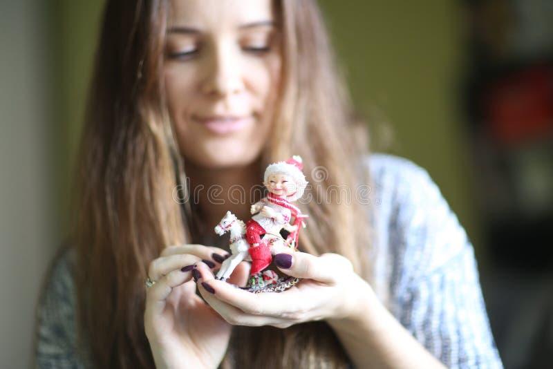 年轻俏丽的妇女在手上拿着在摇马的小的逗人喜爱的矮子玩具,圣诞节玩具 库存照片
