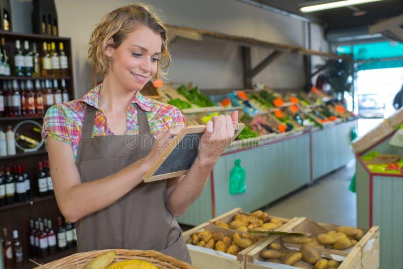 年轻俏丽的妇女在果子商店工作 免版税图库摄影