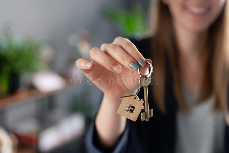 年轻俏丽的妇女微笑 议院钥匙在妇女手上 现代轻的大厅内部 不动产,抵押权,移动的家 库存照片