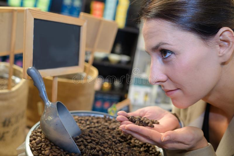 年轻俏丽的妇女用烤咖啡豆 免版税库存照片