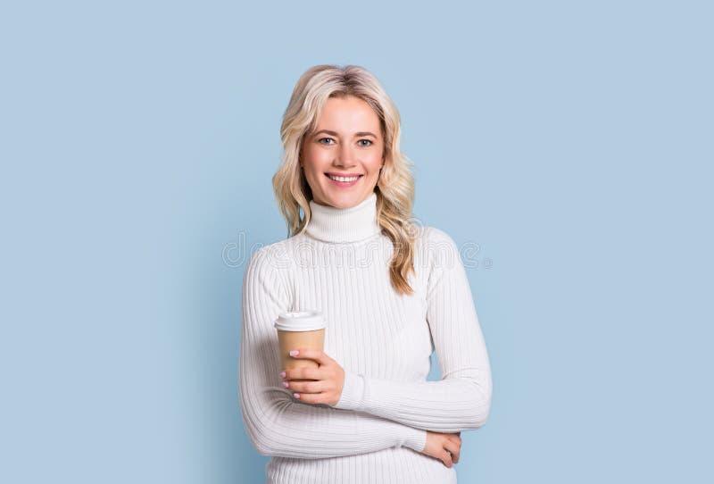 年轻俏丽的妇女用进来的咖啡,在纸,在蓝色背景的聚苯乙烯泡沫塑料杯子 图库摄影