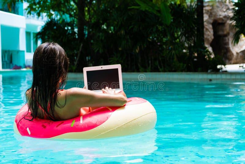 年轻俏丽的妇女自由职业者浮动在海或在一个游泳的圈子的水池 女孩在放松 免版税图库摄影