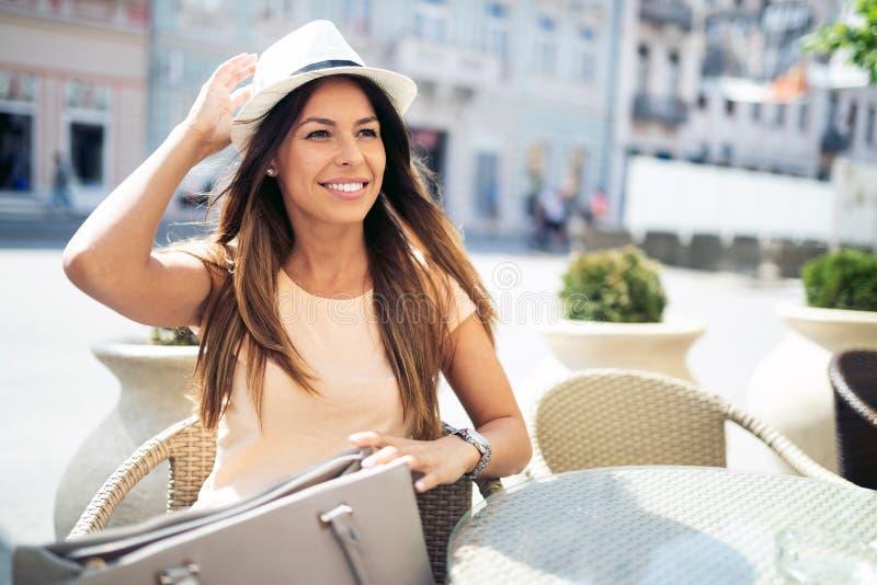 年轻俏丽的妇女饮用的热奶咖啡,在咖啡馆的咖啡户外 免版税库存照片
