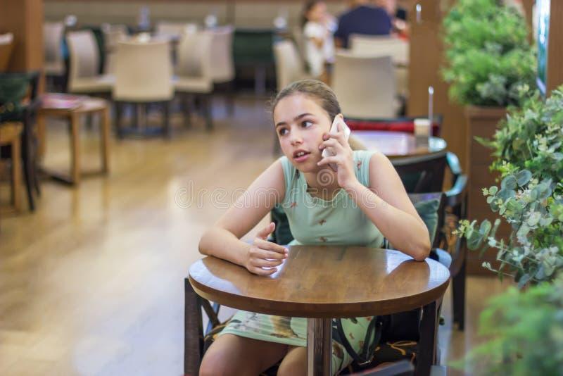 年轻俏丽的少年女孩谈话由在一个咖啡馆的电话在购物中心 库存照片