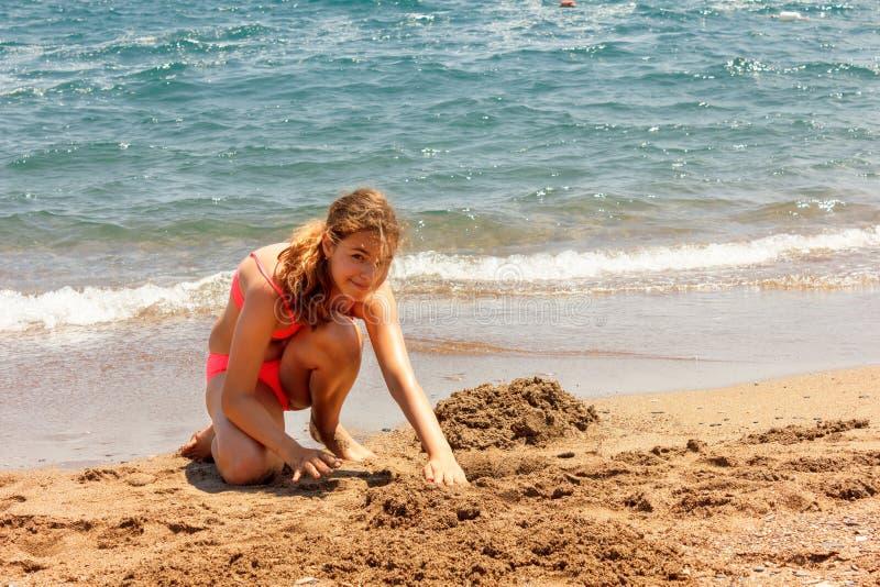 年轻俏丽的少年晒黑了修造在海滩的女孩沙子城堡近由海 免版税库存照片