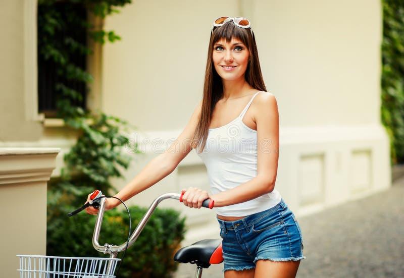 年轻俏丽的性感的与与红色自行车的妇女减速火箭的行家样式室外画象有乐趣和微笑 库存图片