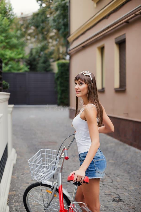 年轻俏丽的性感的与与红色自行车的妇女减速火箭的行家样式室外画象有乐趣和微笑 免版税图库摄影