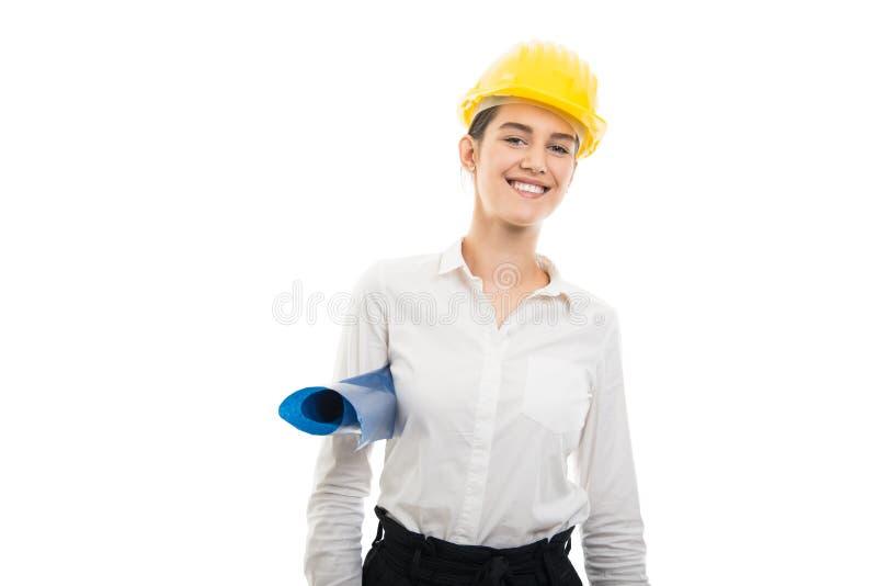 年轻俏丽的拿着图纸的妇女建筑师佩带的盔甲 免版税库存图片