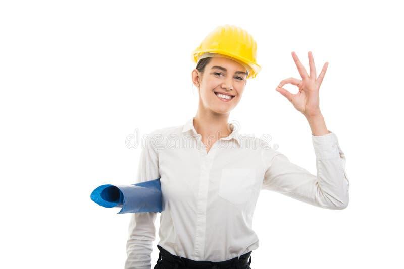 年轻俏丽的拿着图纸s的妇女建筑师佩带的盔甲 免版税库存图片