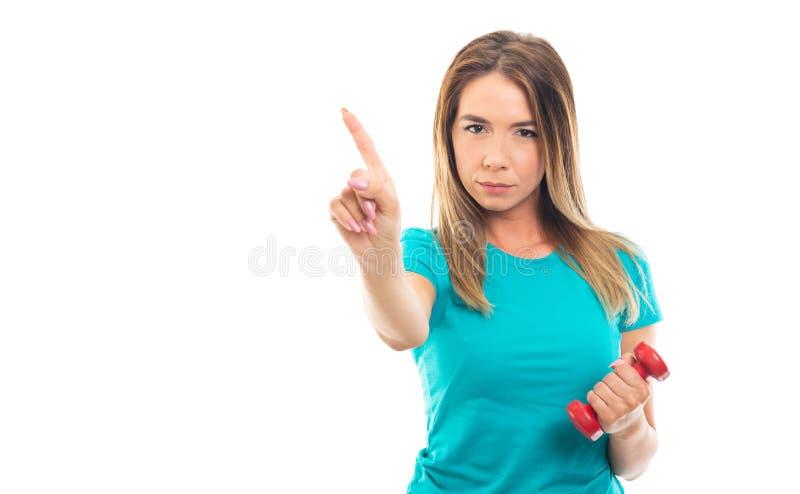 年轻俏丽的显示与手指的女孩佩带的T恤杉姿态 库存照片