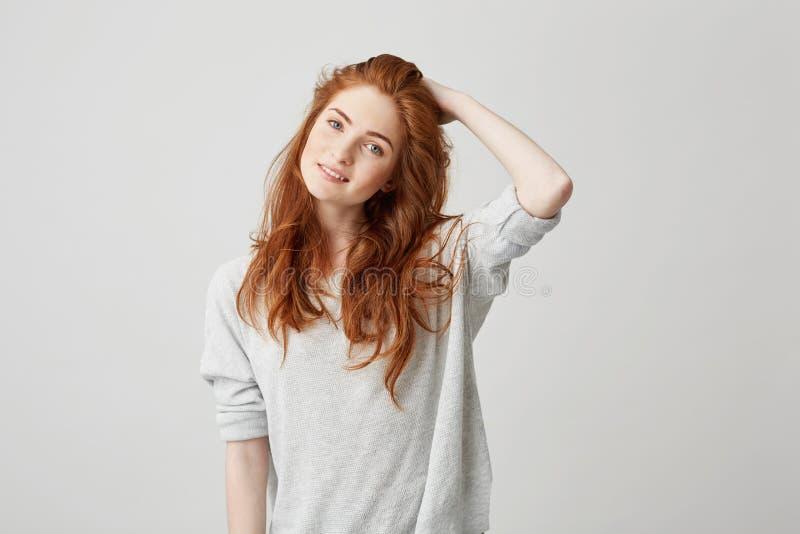年轻俏丽的红头发人女孩画象有看在白色背景的雀斑的照相机微笑的感人的头发 免版税库存图片