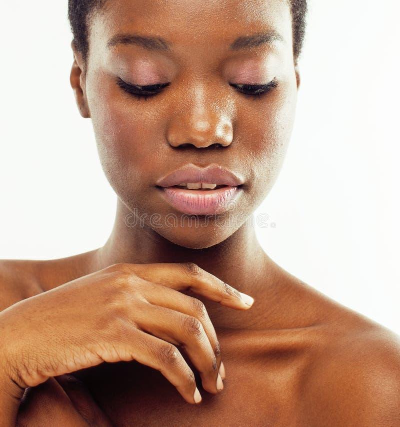 年轻俏丽的非裔美国人的在白色背景隔绝的她的皮肤妇女赤裸采取的关心,医疗保健人 免版税库存图片