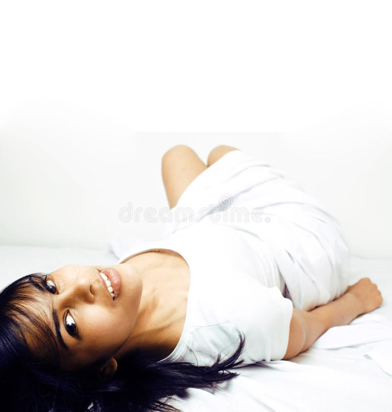 年轻俏丽的tann妇女在获得白色的板料中的床上乐趣,设法睡觉,无所事事  免版税图库摄影