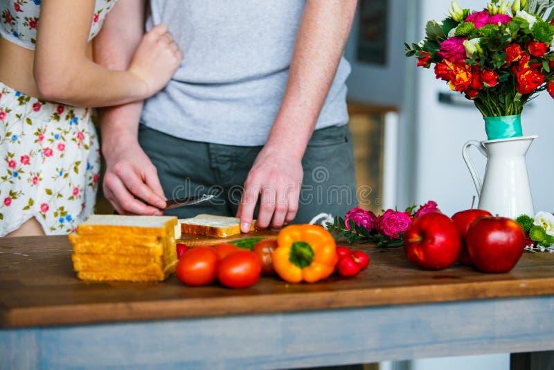 年轻做早餐的人和妇女在厨房里 免版税图库摄影
