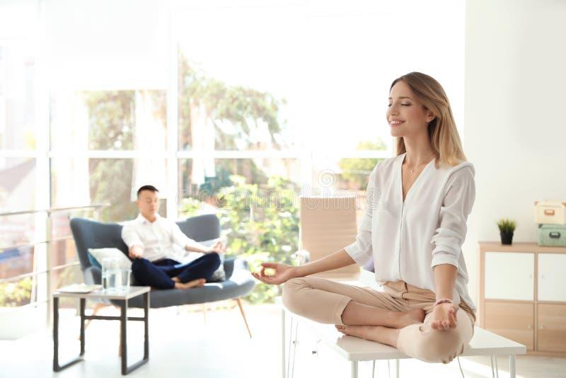 年轻做瑜伽的女实业家和她的同事 库存图片