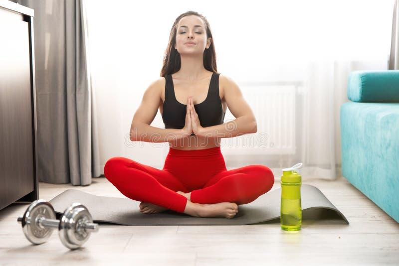 年轻健美的女性穿运动装,每天在家做地板上的晨练,运动的生活方式 免版税图库摄影