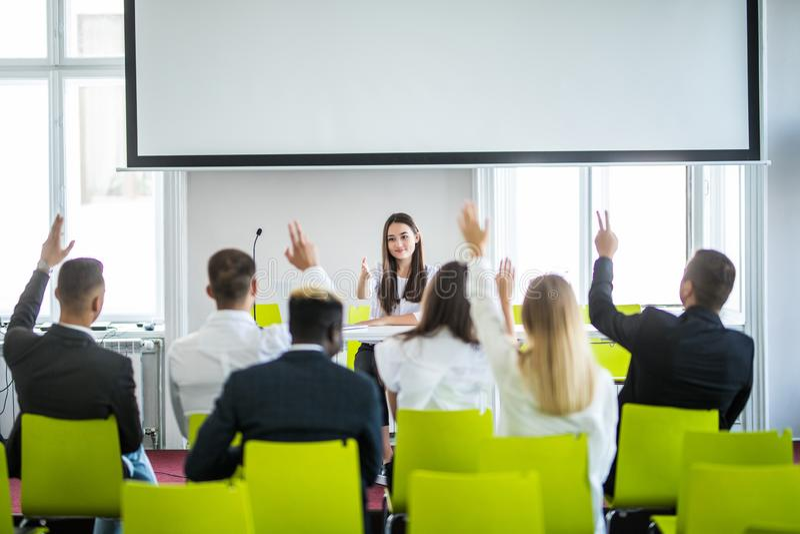 年轻偶然亚洲女实业家领导做介绍和请求观点在会议 商业主持会议服务台查出在白色 免版税库存图片