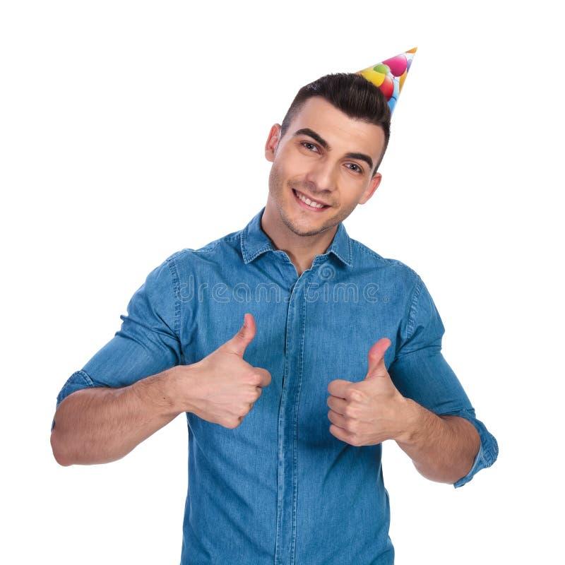 年轻偶然人佩带的生日帽子做好标志 库存图片