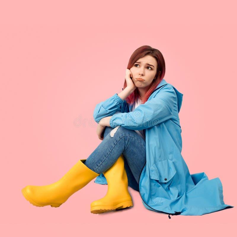 年轻免受雨和高黄色胶靴保护的美女佩带的春天雨衣 免版税库存图片