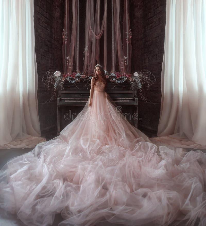 年轻公主在一架非常老钢琴的背景的哥特式屋子站立 女孩有一个冠和一豪华 免版税图库摄影