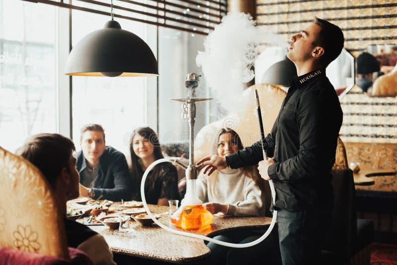 年轻公司获得乐趣并且吃着在酒吧 抽水烟筒,沟通在一家东方餐馆 免版税库存图片