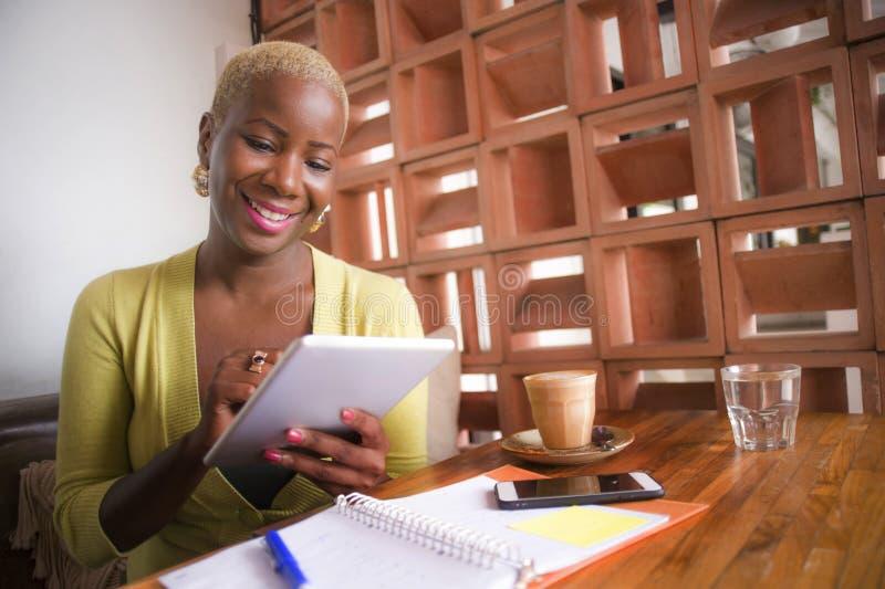 年轻典雅和美丽的黑人非裔美国人的女商人在网上与数字式片剂垫一起使用在咖啡店微笑的ha 免版税库存照片