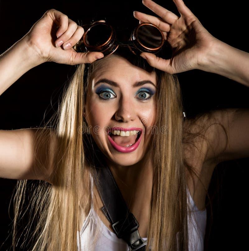 年轻冲动的性感的在黑暗的背景的妇女佩带的焊接的玻璃 库存图片