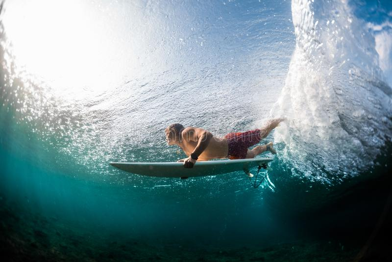 年轻冲浪者潜水在海浪下 库存图片