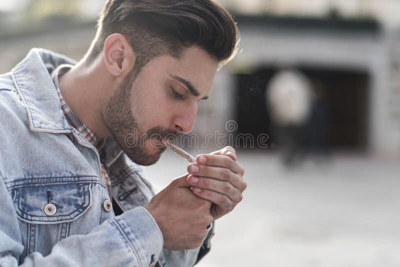 年轻凉快的人抽烟的雪茄 免版税库存图片