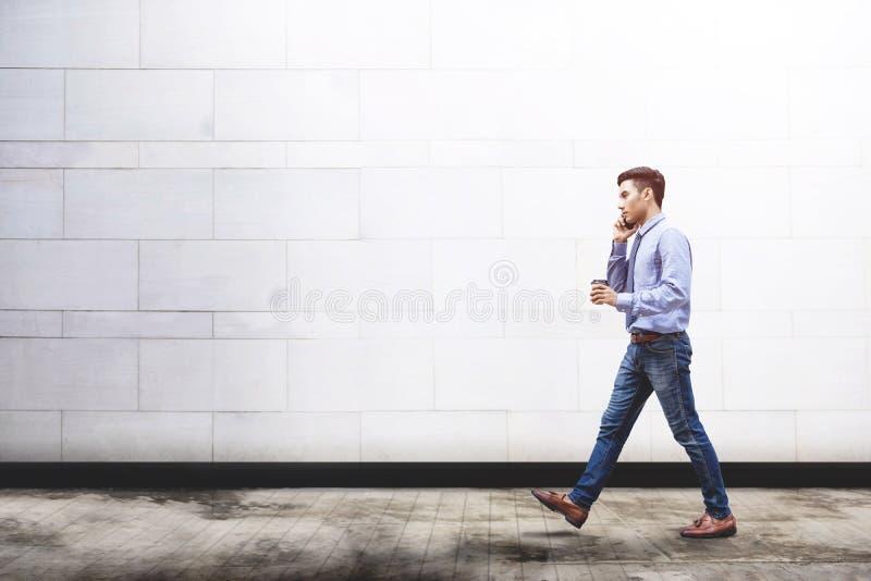 年轻刺激商人谈话通过巧妙的电话,当走出去时 免版税库存图片