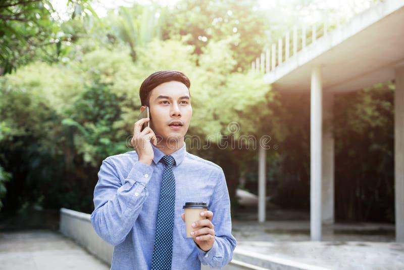 年轻刺激商人谈话通过智能手机,当步行outd时 免版税库存图片