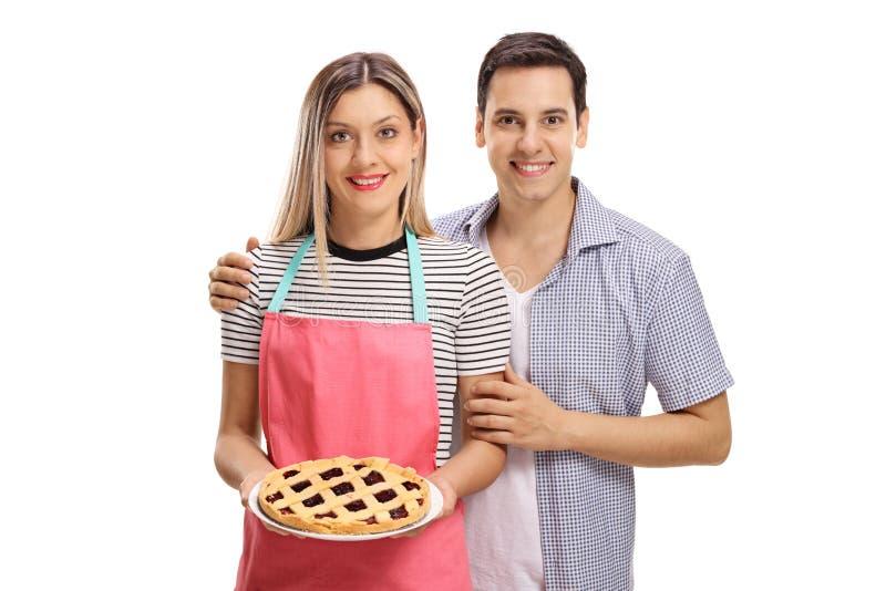 年轻加上一个新近地被烘烤的饼 免版税库存图片