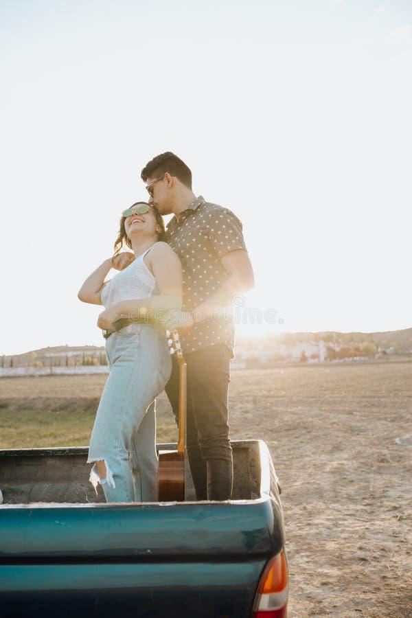年轻加上亲吻在日落的吉普4x4汽车顶部的吉他 库存图片