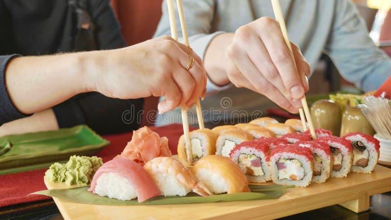 年轻加上筷子在一家日本餐馆采取从一块板材的寿司 免版税库存照片