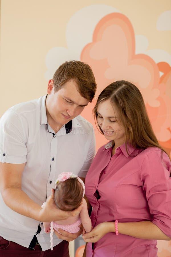 年轻加上逗人喜爱的矮小的婴孩 在家拿着他们新出生的小女儿的微笑的母亲和父亲 夫妇亲吻 拥抱 库存图片