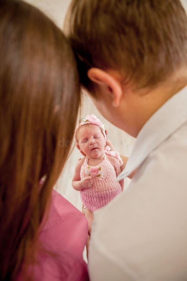 年轻加上逗人喜爱的矮小的婴孩 在家拿着他们新出生的小女儿的微笑的母亲和父亲 夫妇亲吻 拥抱 免版税库存照片