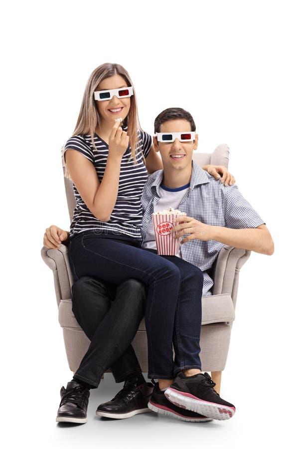 年轻加上3D坐在扶手椅子的玻璃和玉米花 免版税库存图片