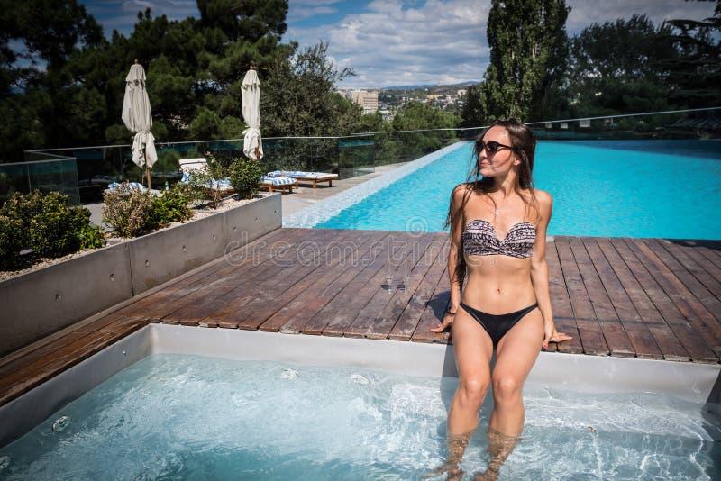 年轻匀称妇女在水池附近坐在太阳光芒下 免版税库存图片