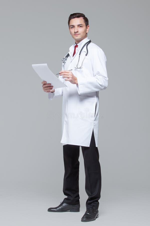 年轻医生全长画象白色制服的有听诊器藏品文件夹的 库存图片