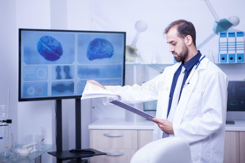 年轻医生转动的页与分析在他的剪贴板在脑子问题的一个实验室 免版税库存照片